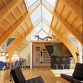 An open-plan living room with a dining area and a mini kitchen in a converted attic with skylights