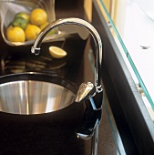 A stainless steel sink in a black granite work surface