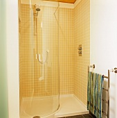 A semi-tiled shower cubicle with a curved wall and a stainless steel heated towel rail