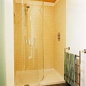 Gelbgeflieste Dusche mit gebogener Glastrennwand und Handtuchtrockner aus Edelstahl