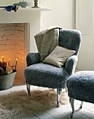 An armchair and a matching stool with fluffy grey covers next to a fireplace in a traditional atmosphere