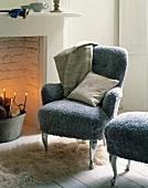 Sessel und passender Hocker mit grauem flauschigen Bezug neben Kamin im traditionellem Ambiente