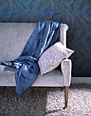 A blue stain quilt on a lilac coloured sofa on a fluffy rug