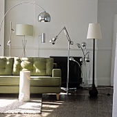 A collection of floor lamps displaying a range of materials and style and a sofa in front of a fireplace