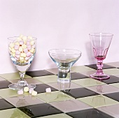Various stemmed glasses, one filled with sweets on chessboard patterned tiles