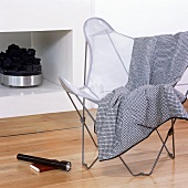A quilt on a Bauhaus bat-wing chair in front of a fireplace