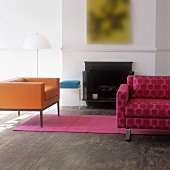 An orange cubic armchair and a pink patterned sofa in front of a fireplace in a traditional atmosphere