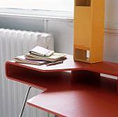 Roter Designer Schreibtisch und gelb lackierte Kiste mit Öffnungen