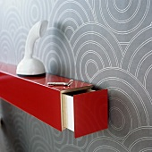 A white telephone on red shelf with an open drawer mounted on a wall hung with a geometric pattern
