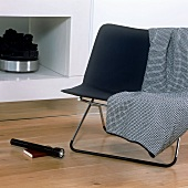 A chair with a stainless steel frame in front of a fireplace