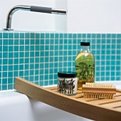Bathing utensils on a shelf across a bath tub