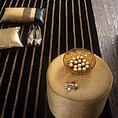 A stool, decorative cushions and a pair of ladies shoes on a stripped rug