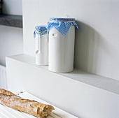 White storage jars with blue and white checked fabric lids