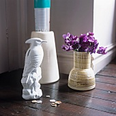 A white bird figurine next to a vase on flowers on a wooden floor