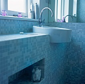 A wash basin under a window in a bathroom decorated with mosaic tiles
