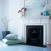 Floor cushions next to a fireplace decorated with stucco