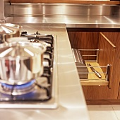 A stainless steel pot on a gas hob and an open drawer with a bread bin inside it