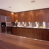 An illuminated kitchen with wooden cupboards and a stainless steel fridge