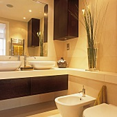 A bathroom with two wash basins and a bidet