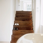 Two pairs of slippers on a wooden stair