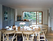 A table laid for breakfast on a light wooden table with classic chairs in an open-plan dining room in front of a kichten counter