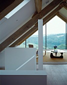 A converted attic room with a coffee table in front of a glazed gable with an impressive view