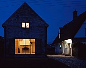 A renovated house by night with illuminated windows and a view of a fireplace