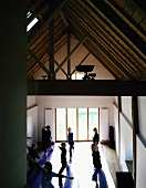 A yoga class in a renovated attic with wooden beams