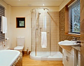 A spacious bathroom with a curved glass shower door and a washstand in front of a window