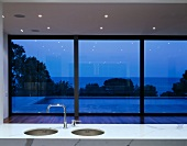 A shiny white marble surface with a kitchen sink in front of a window in a minimalistic room and a view of a pool by night