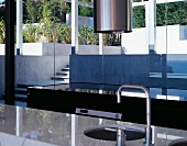 A sink set into a shiny stone work surface in a modern house with a view through a window onto a terrace