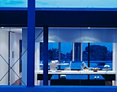 A contemporary house by night with a view through a window in an illuminated kitchen