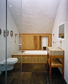 A view through an open glass door into a modern bathroom with bamboo panelling in front of the bathtub and brown marbled stone tiles