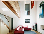 Red leather corner sofa beneath gallery, wall opening with glass balustrade and staircase