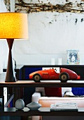 Retro toy car and lamp on wooden shelf