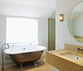 Modern stone sink and free-standing vintage bathtub with designer floor-mounted tap fittings
