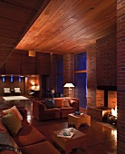 Evening atmosphere in modernist house with wooden ceiling and sofas next to fireplace in brick wall