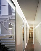 Narrow hallway with doorways to rooms and windows onto stairwell