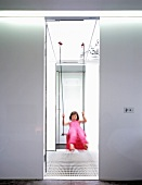 Blurred view through doorway of girl in pink dress on swing in light stairwell