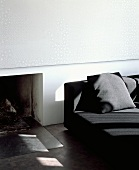 Wall panel with subtle white and pastel grey pattern above open fireplace next to modern black sofa