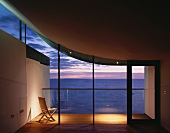 Chair on illuminated terrace beyond empty living room with view of evening sky under a floating roof curving upwards at one side