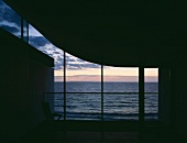 Sculptural, unlit interior with view through glass facade to evening sky over the sea