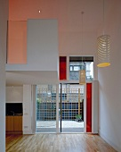 Entrance with lantern-like pendant lamps, strip parquet and wide glass door with red elements