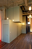 Interlocking cubist rooms in large hall with wooden floor and pendant lights between roof beams