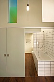 View of bathroom installed in loft with wooden floors below an interior window illuminated with coloured light