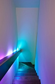Walls of narrow stairway illuminated in different colours by indirect handrail lights