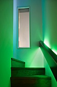 Durch kastenförmiges Geländer mit indirekter Beleuchtung in grünes Licht getauchter Treppenaufgang mit Holzstufen und Blick auf Innenfenster