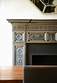 Detail of elegant, classical mantelpiece behind a fine wood table