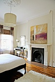 Bedroom with elegant dressing table and modern painting in a old building with stucco and traditional fireplace