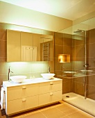 Reflections on glass wall of shower and mirrored cupboard in modern bathroom with two round sit-on basins